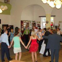 Dual music svatebčané tančí v sále kolečko kolem novomanželů