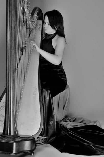 Harfistka Katarina Ševčíková v černých šatech s harfou černobílá
