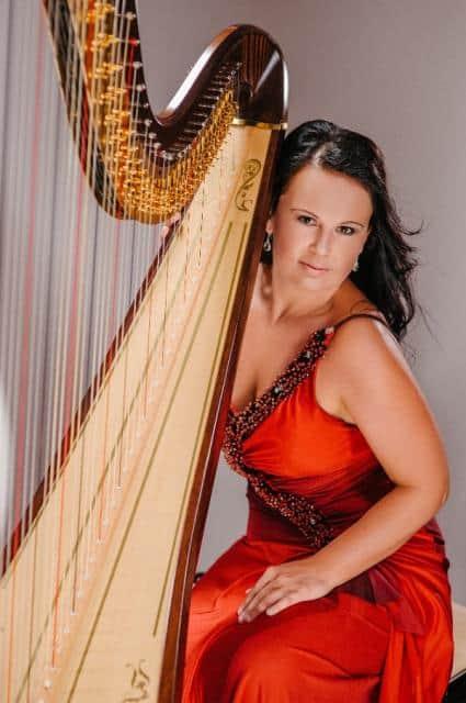 Harfistka Katarina Ševčíková v oranžových šatech s harfou