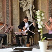 musica di praga hrají v sále s kamennou sochou v pozadí