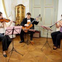 musica di praga hrají v sále se zlatou skříní v pozadí