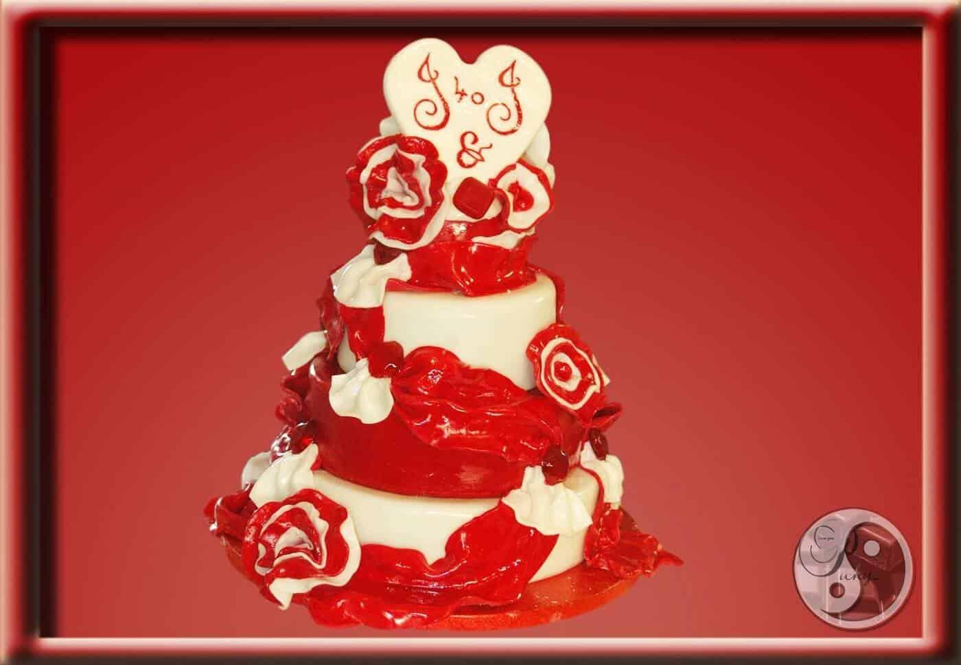 Elegantní dort v rubínově-bílé barvě s drapérií, květy, ručně litými karamelovými rubíny a topperem v podobě srdce z bílé čokolády s vyrytými iniciály.