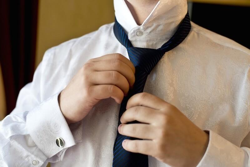 Ženich v košili váže kravatu