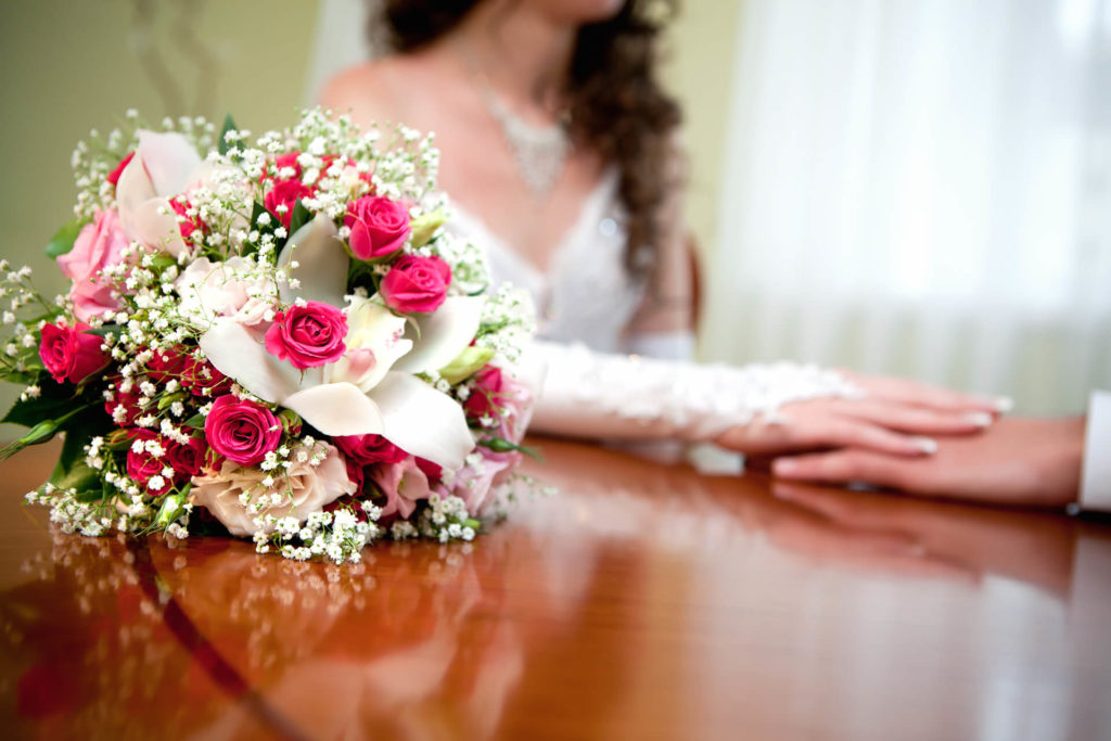 Svatební kytice v pozadí spojené ruce