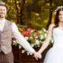 Svatební pár ve stylovém oblečení u dřevěného povozu