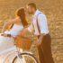 Svatební pár v přírodě se líbá u cestovního kola