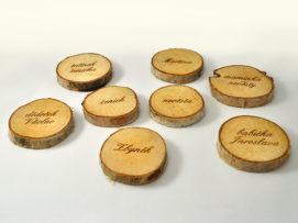 Dřevěná kulatá jmenovka na svatební tabuli se jmény hostů