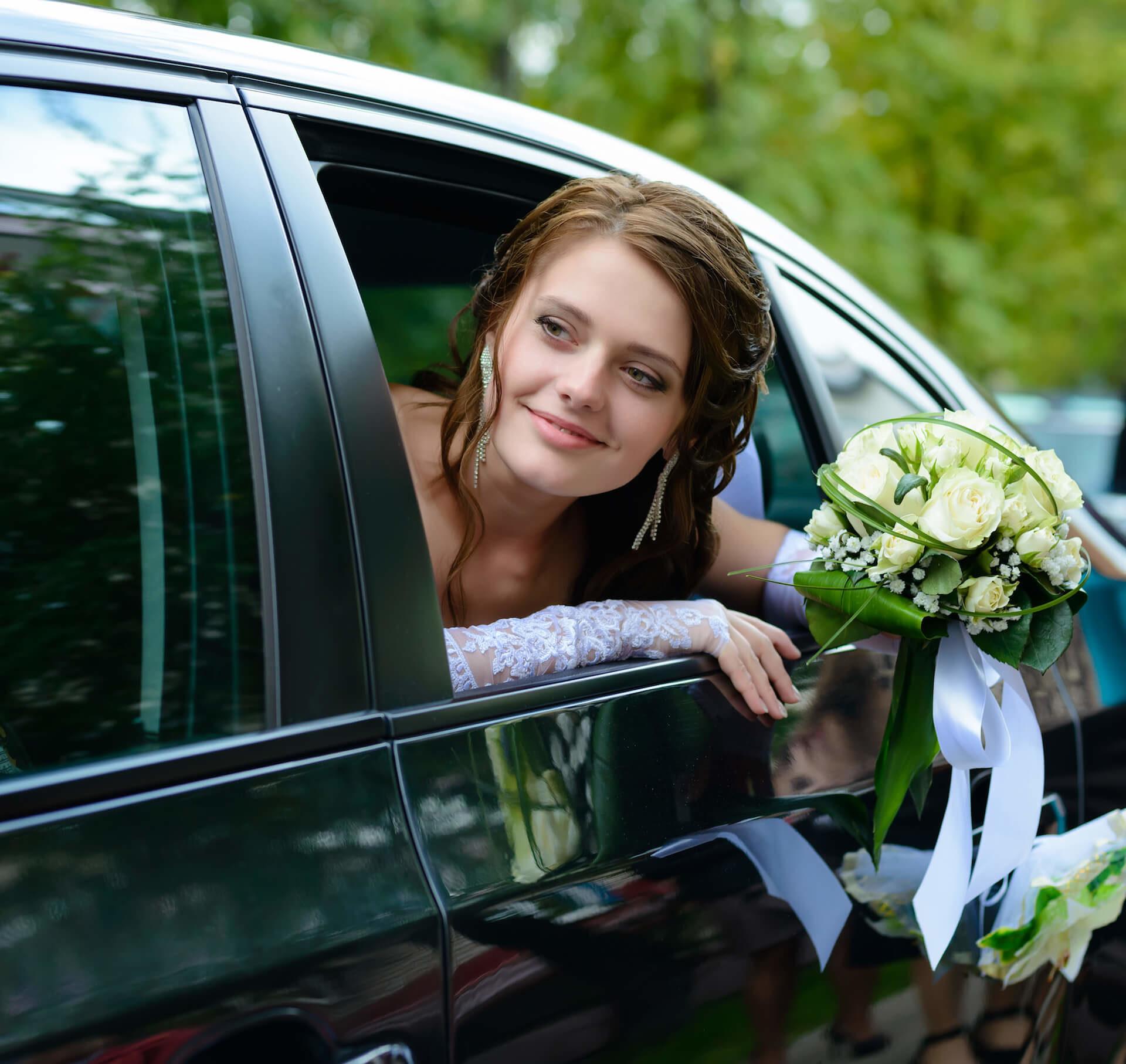 Roztomilá nevěsta s kyticí ve svatebním autě
