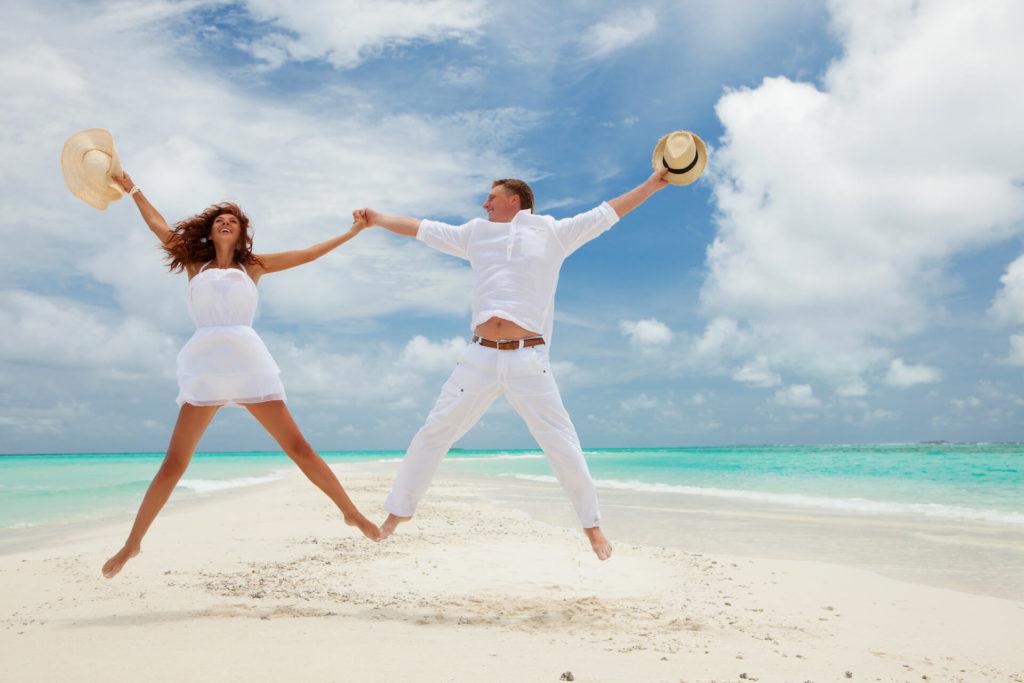 Šťasný pár ve výskoku na písčité tropické pláži