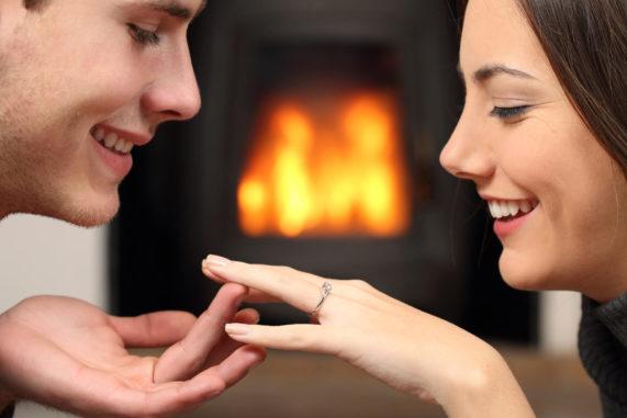 Sympatický pár se zásnubním prstenem u krbu