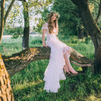 Nevěsta ve svatebních šatech sedí na větvi stromu