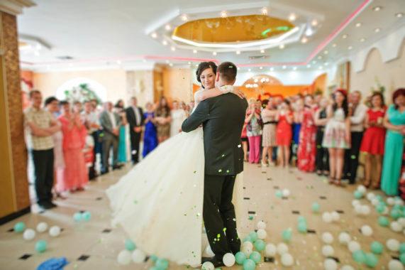 Novomanželé při svatebním tanci v kruhu svatebčanů