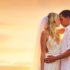 Novomanželé v objetí na břehu moře při západu slunce, úvodní foto