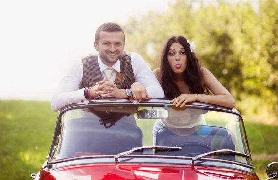 Novomanželský pár jízda autem s vyplazeným jazykem