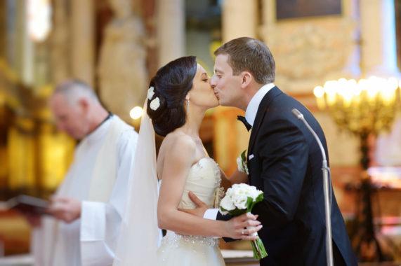 Polibek novomanželů při církevním svatebním obřadu v kostele