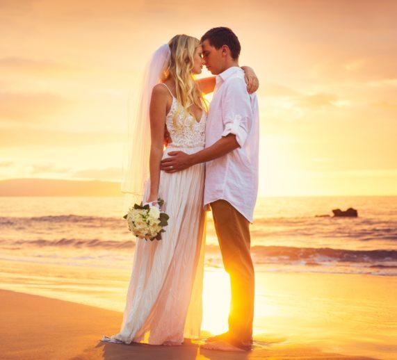 Novomanželé v objetí na břehu moře při západu slunce