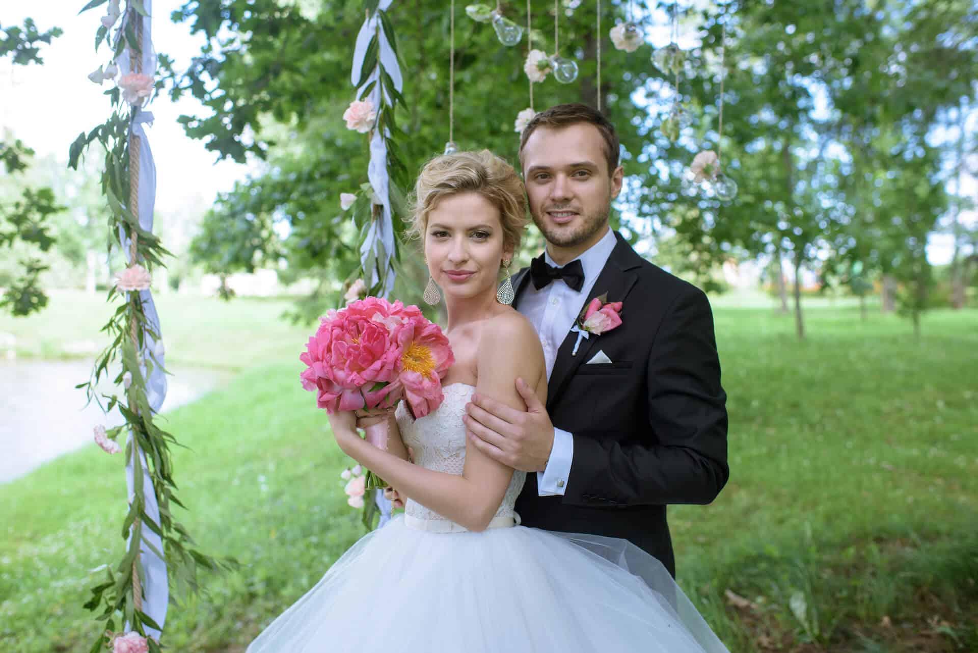 Svatební pár v přírodě, nevěsta s kyticí pivoněk