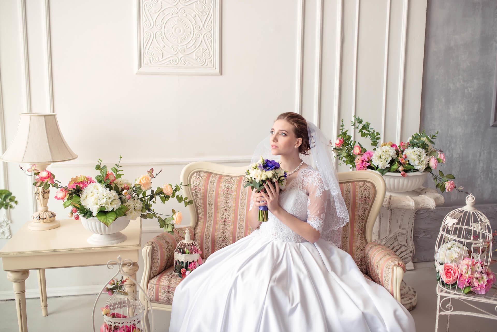 Krásná nevěsta s kyticí v zámecké komnatě