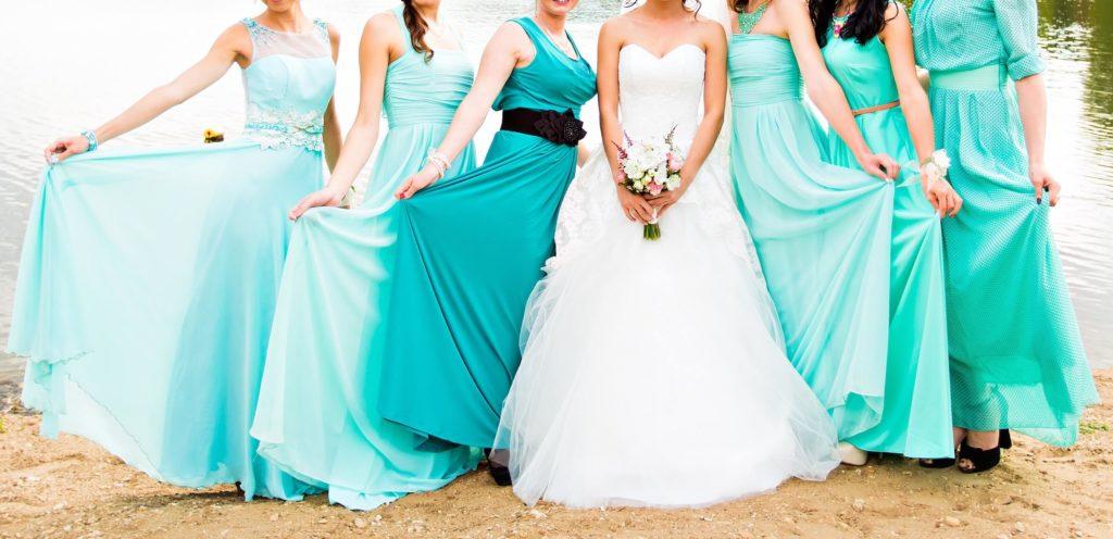 Nevěsta v bílých šatech a družičky v tyrkysových šatech u vody