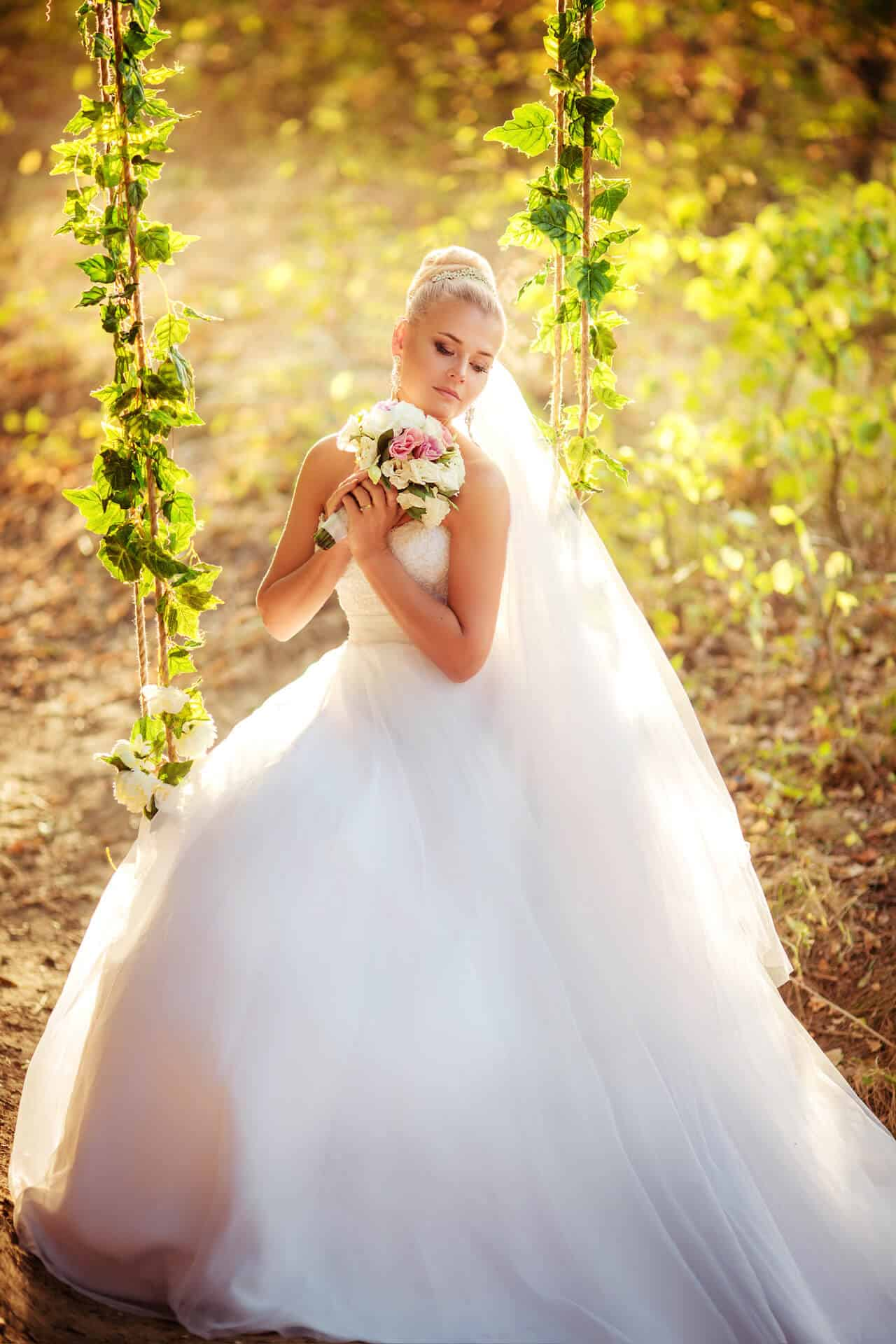 Nevěsta v bílých šatech se svatební kyticí