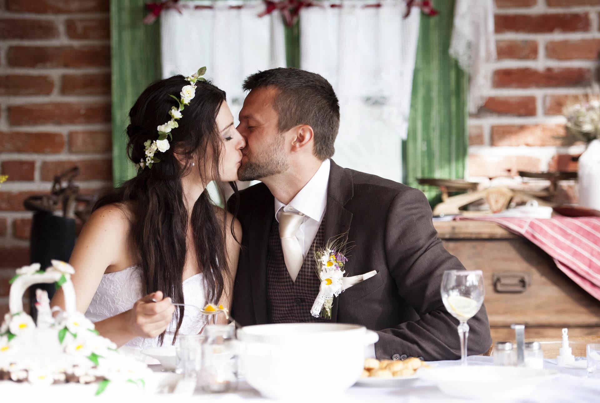 Nevěsta s ženichem při polibku na venkovské svatbě u cihlové zdi