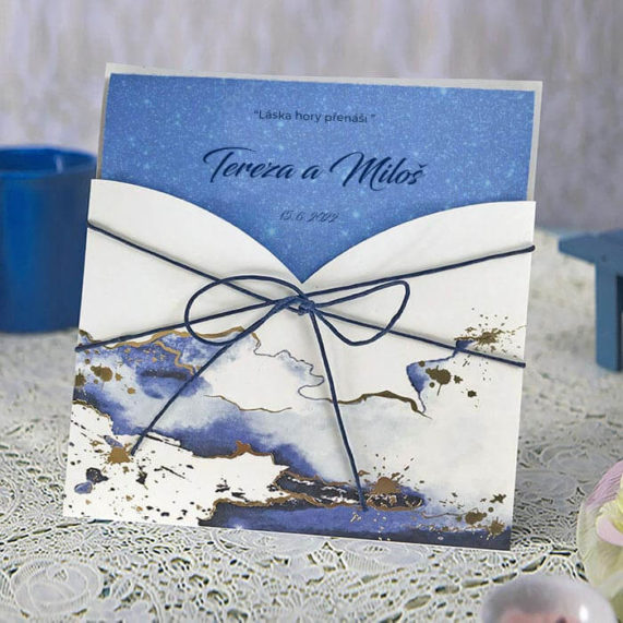 Svatební oznámení s abstraktní modro bílou mlhovinou se zlatými obrysy a provázkem