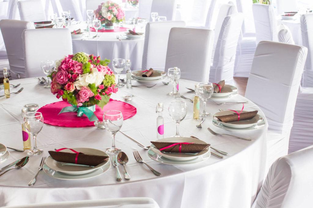 Elegantní svatební tabule s kyticí a bílými potahy na židlích