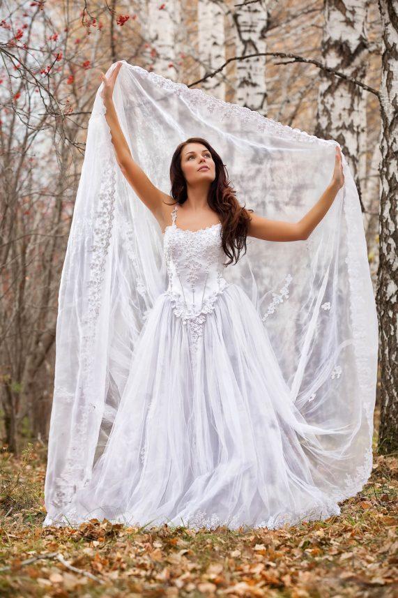 Nevěsta s hnědými dlouhými vlasy s vlečkou v lese