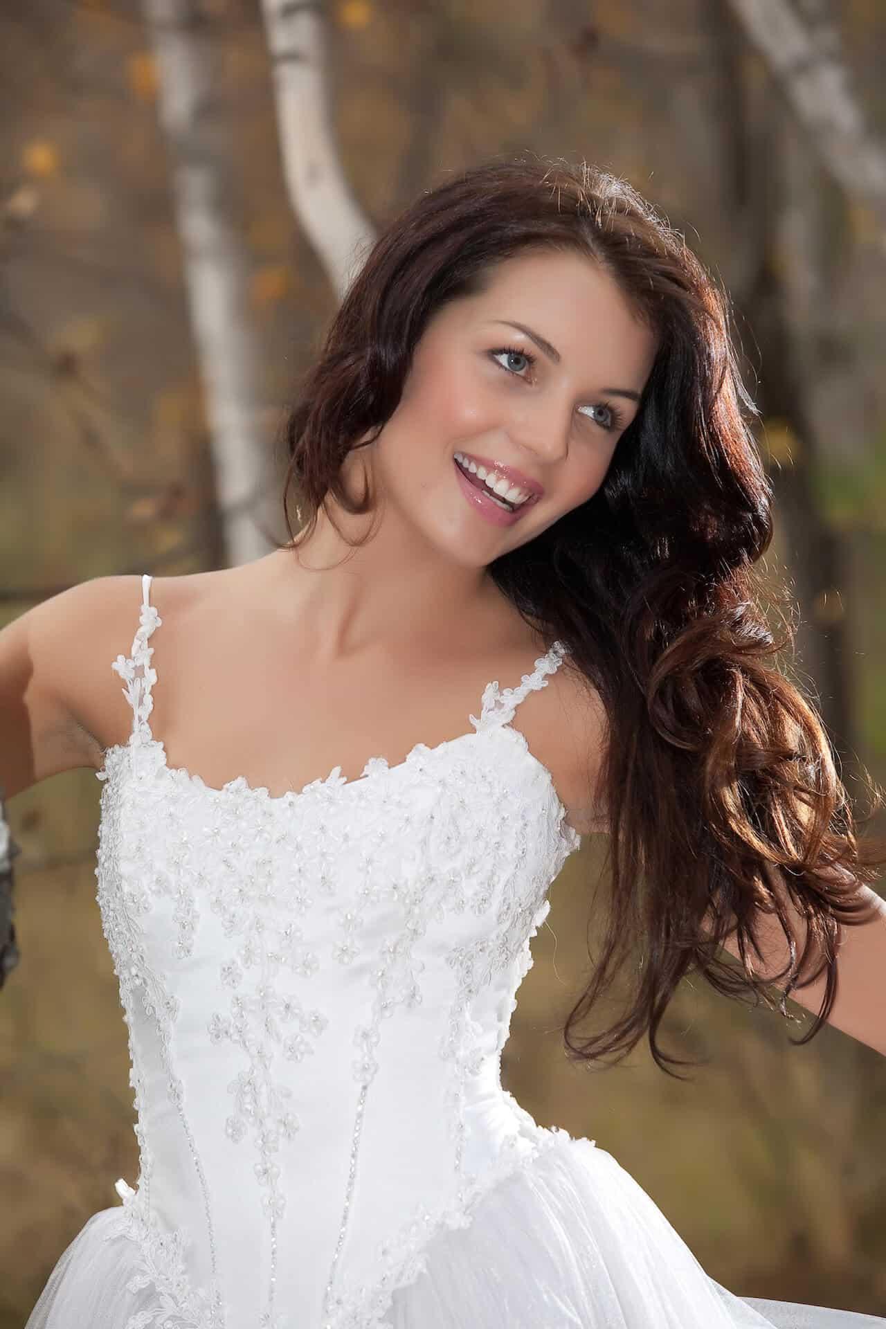Usmívající se nevěsta s hnědými dlouhými vlasy