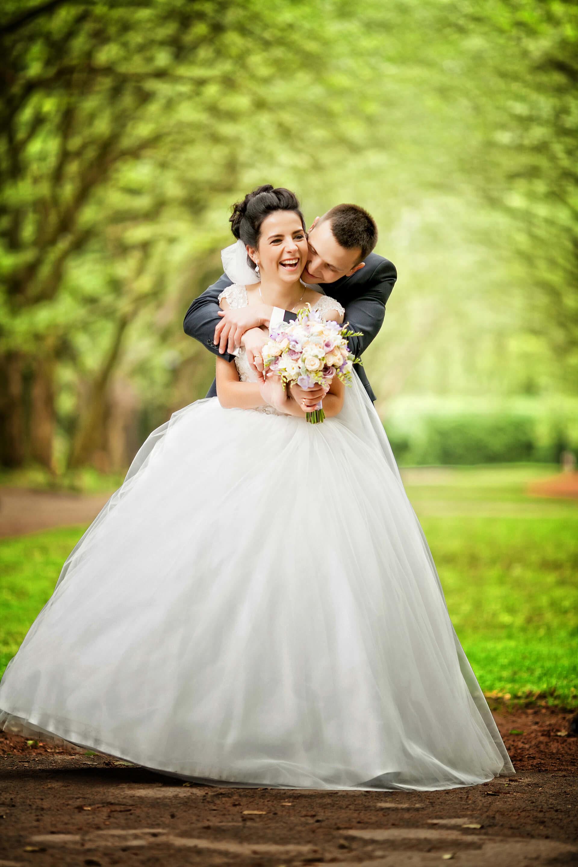 Novomanželský radostný pár se objímá v parku