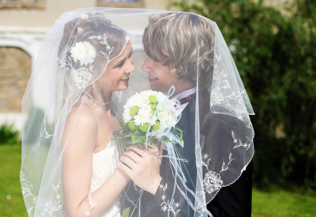 Krásný svatební pár za závojem