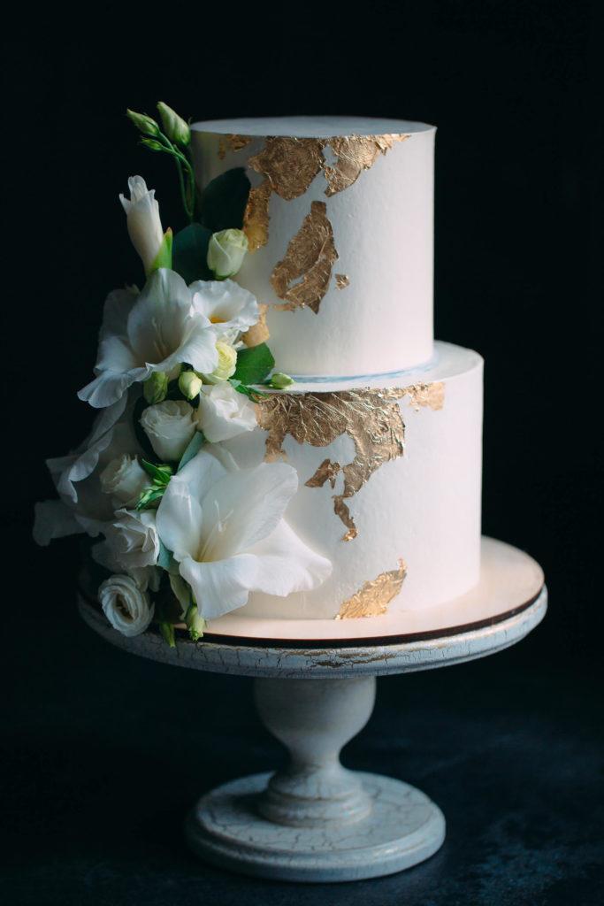 Dvoupatrový svatební dort s květinami na stojanu