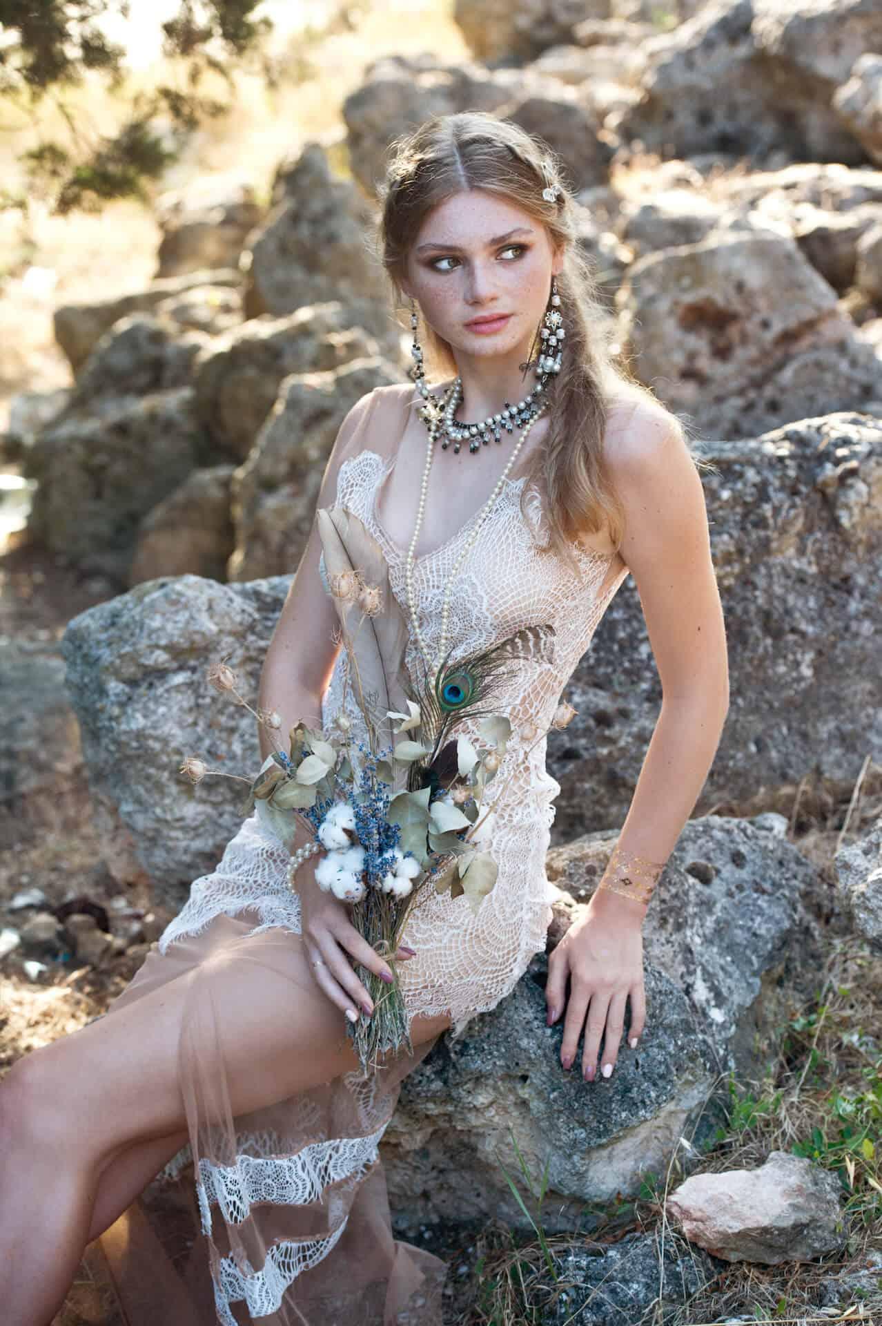 Krásná nevěsta ve svatebních šatech ve stylu BOHO s kyticí