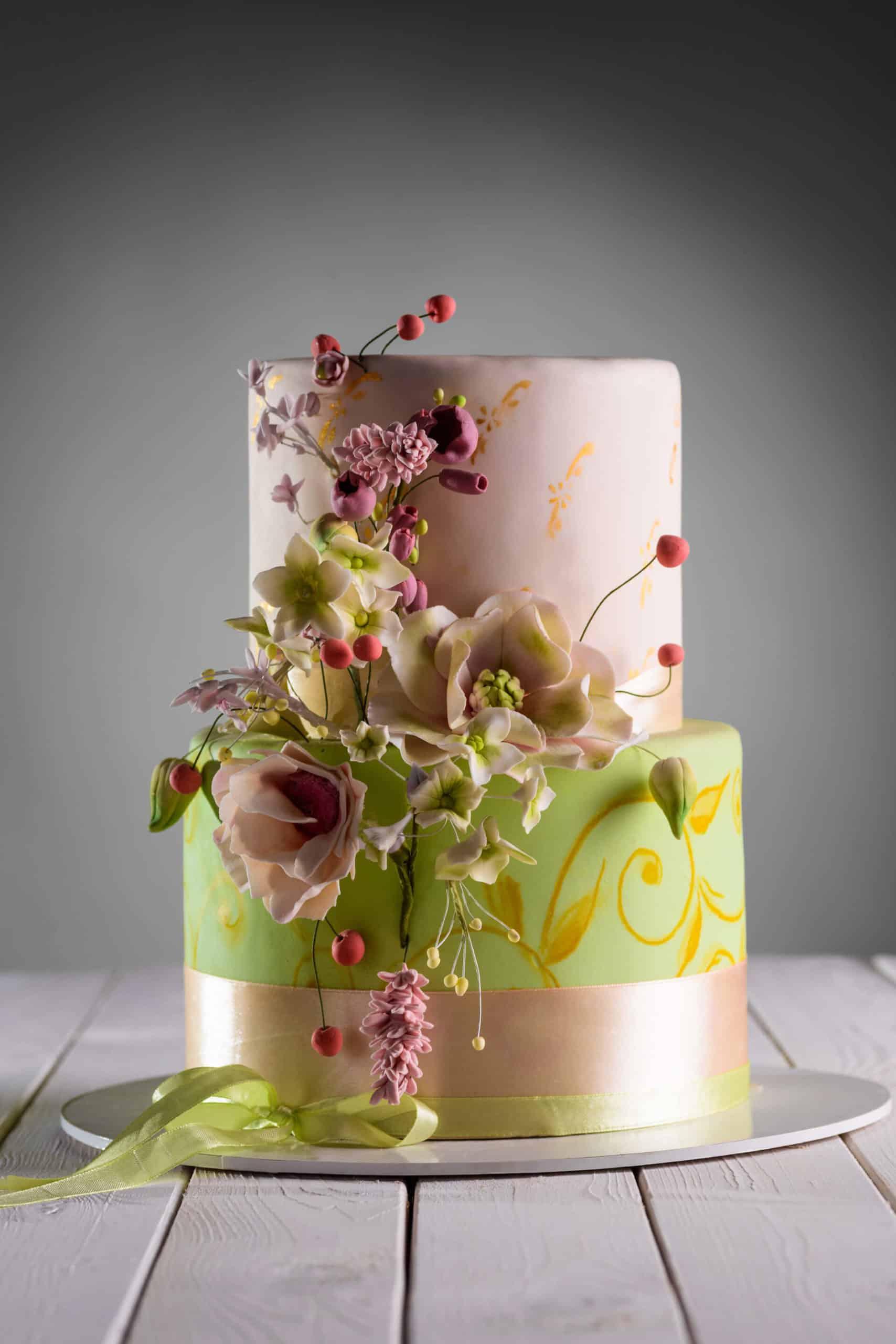 Krásně zdobený dvoupatrový svatební dort v zelenozlatém hávu