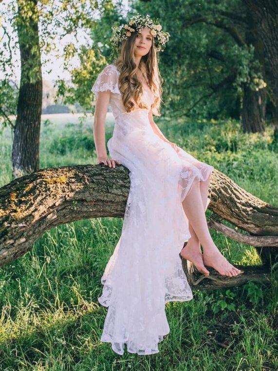 Bosá nevěsta sedící na větvi ve svatebních Boho šatech