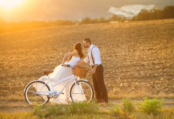 Líbající se novomanželský pár s kolem na cestě