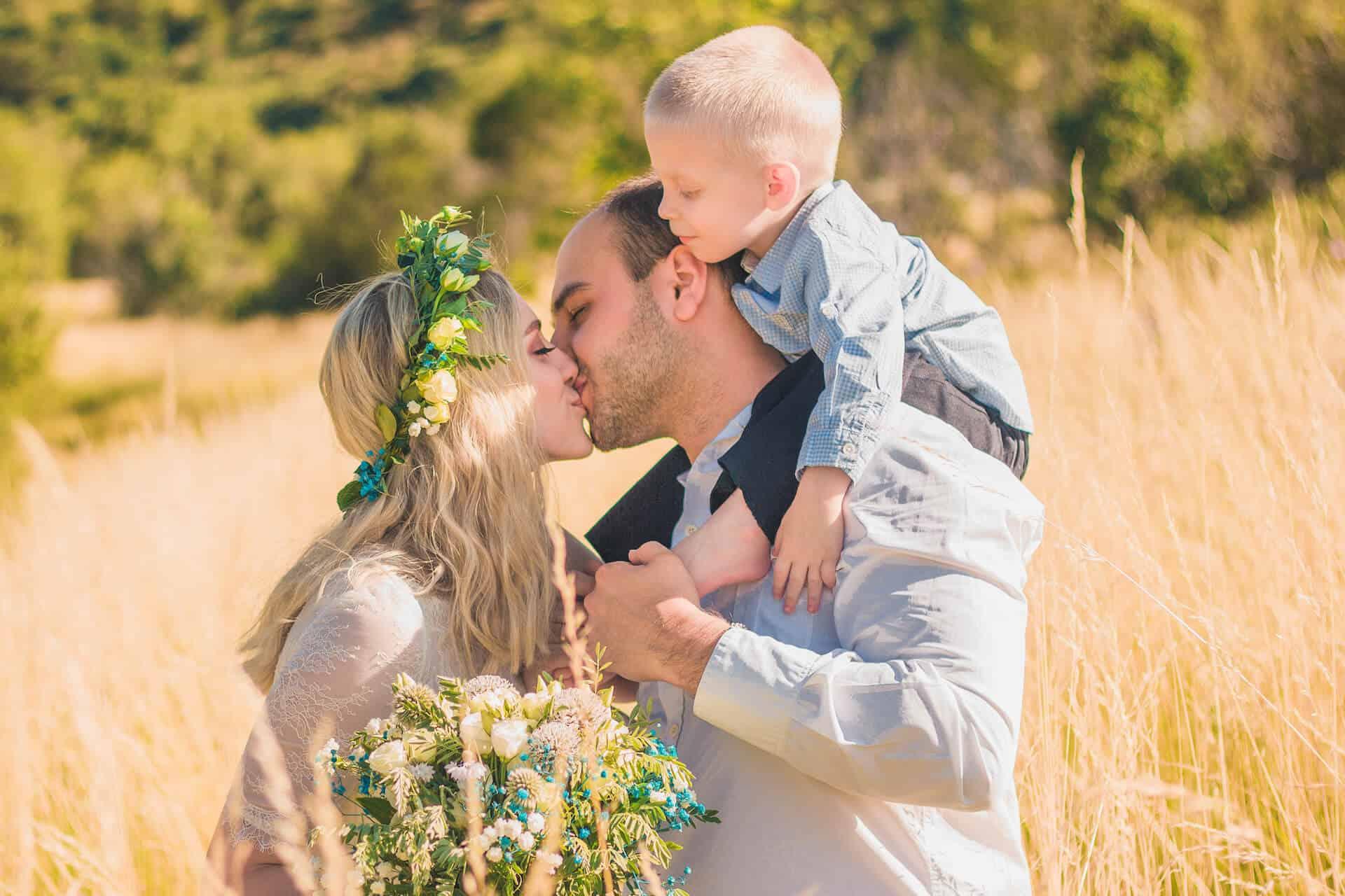 Novomanželský polibek na louce se synem