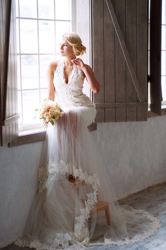Nevěsta sedící v okně s kyticí v krásných svatebních šatech