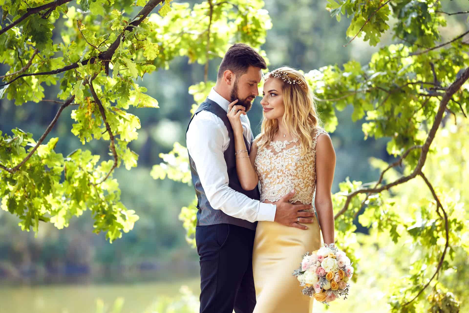 Zamilovaný novomanželský pár pod dubem