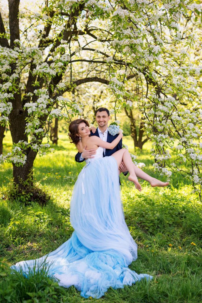 Svatební pár v rozkvetlém sadu, ženich s nevěstou v náručí