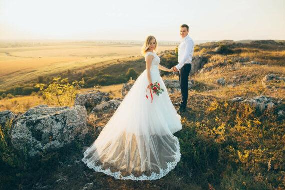 Nevěsta s vlečkou a ženichem se fotí na kamenech