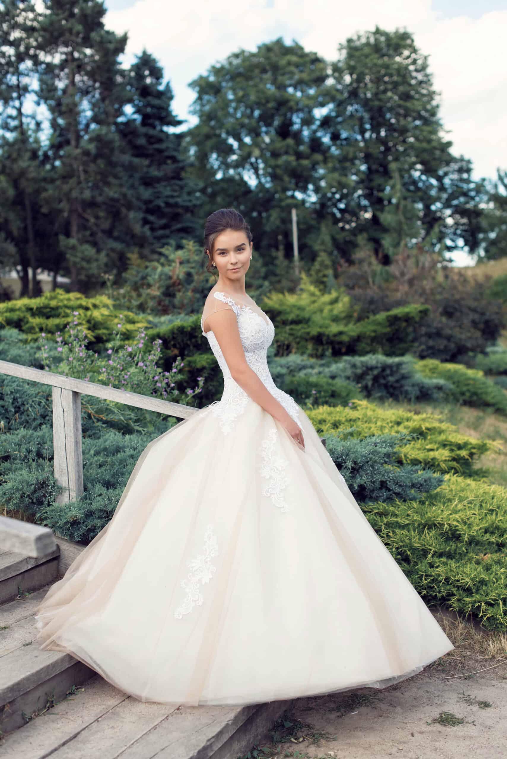 Půvabná nevěsta v zahradě ve svatebních šatech
