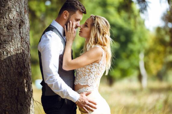 Nevěsta a ženich v objetí pod velkým stromem